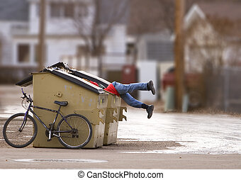 Urban poverty - man with a bike looking in a dumpster