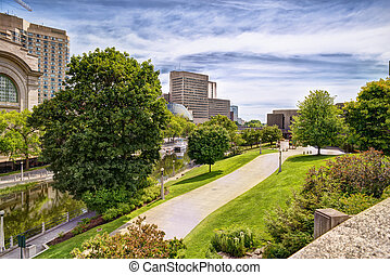 Urban scene of buildings and Rideau canal, cloudy sky in...