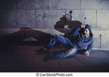 alcoholic grunge man sitting on ground street corner drinking alcohol bottle