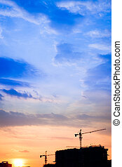 Urban scenic - Industrial construction cranes and building silhouettes at sunset