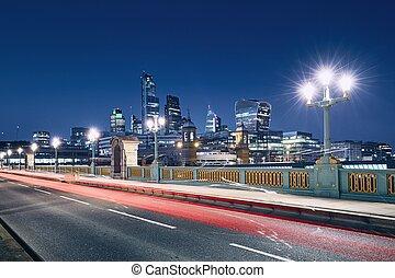 Urban skyline of London - Light trail of car on bridge...