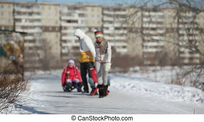 Urban sledge ride - Parents giving their children a sledge ...