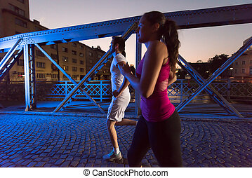 couple jogging across the bridge in the city