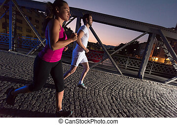 couple jogging across the bridge in the city - urban sports,...