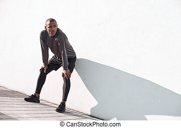 Urban sports. Young man is doing warming up before running in the city on a morning