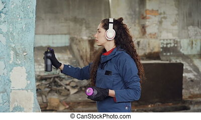 Urban street artist in headphones is listening to music and...