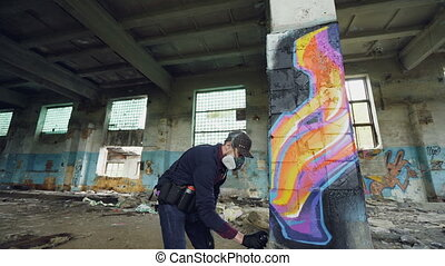 Urban street artist is painting graffiti in abandoned building with dirty walls and windows, he is using paint spray. Modern artwork and creative people concept.