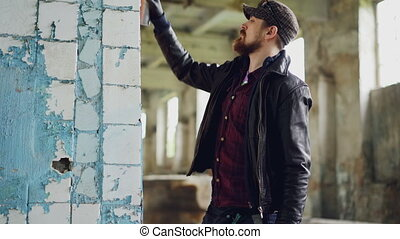 Urban street artist is standing near damaged column inside empty building and painting using aerosol paint spray. Modern art and creative young people concept.