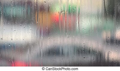Urban street with blurred objects and raindrops on window...
