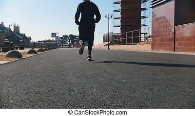 Urban streets. An athletic man running on the street. Mid...