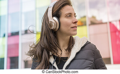 urban style, girl in the street listening to music with headphones on her head, she wears a long hair to the wind and winter jacket