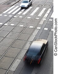 urban traffic concept - city street with a crossing, rail, motion blurred cyclist
