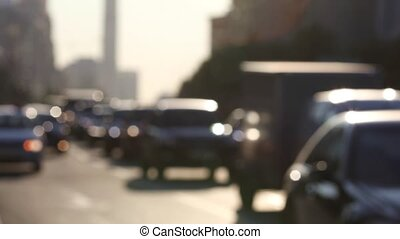 Blurred video shot of urban traffic during rush hour on town streets at sunset. Real time
