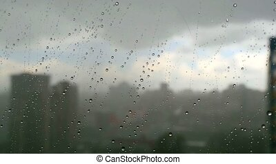 Urban view of rain drops falls on a window during a stormy...