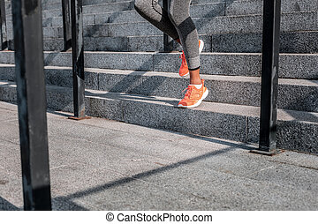 Nice young woman running down the stairs