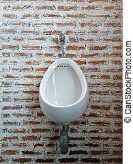 Urinal on brick wall