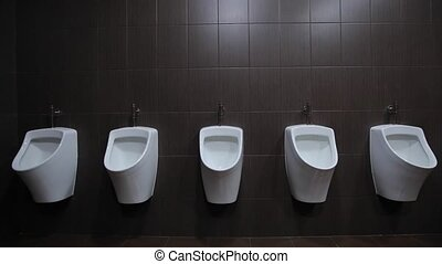 Urinals are fixed on a white wall, gray tiles on the walls,...