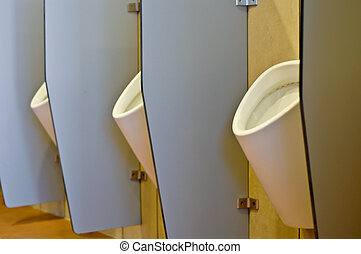Urinals behind partitions in a toilet in office building
