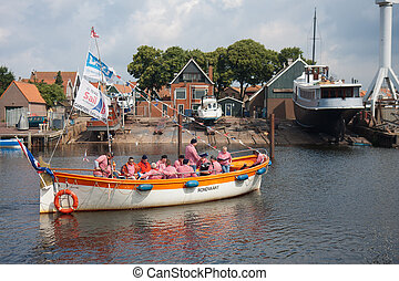 URK, THE NETHERLANDS - JUN 11: A tourist vessel with the members of a traditional sailors choir singing a shanty song at a holiday of Urk on June 1, 2011 in the harbor of Urk, the Netherlands