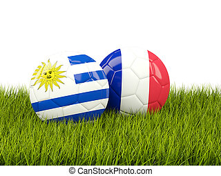 Uruguay vs France. Soccer concept. Footballs with flags on green grass