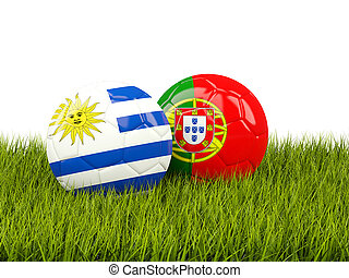Uruguay vs Portugal. Soccer concept. Footballs with flags on green grass