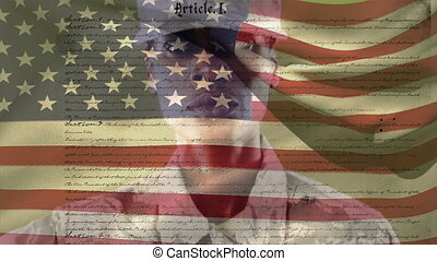 Animation of U.S. flag waving with U.S. Constitution text rolling over African American soldier saluting on green background. United States of America flag and holiday concept digital composition