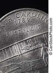 "US American coin with wording ""First Flight"" on black background"