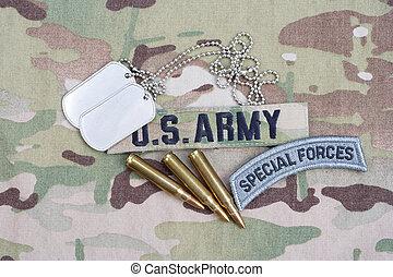 US ARMY special forces tab, flag patch, with dog tag and 5.56 mm rounds on camouflage uniform