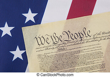 """Close up of the U.S. Constitution document with """"We the People"""" on an American flag."""