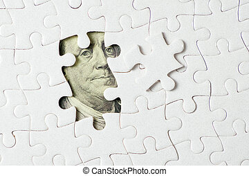 US dollar banknote under jigsaw puzzle