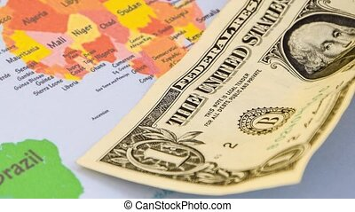 US dollar banknotes on globe world map, American investment and trading, concept of american policy and influence 4k Zoom in