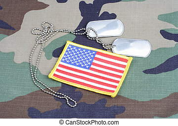 US flag patch with dog tags on woodland camouflage uniform