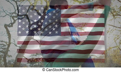 US flag waving against father carrying his son on his ...