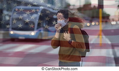 Animation of US flag waving over Caucasian woman wearing a face mask, coughing. Covid-19 coronavirus national health safety concept digital composite