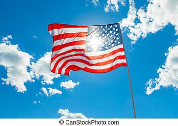 US flag with cumulus clouds and blue sky on background