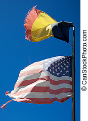 Flags from United States and Belgium floating in the wind with blue and clear sky