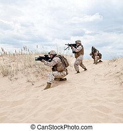military operation - US marines run through the desert...