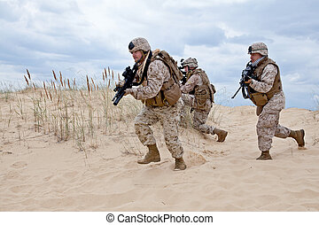 military operation - US marines run through the desert...