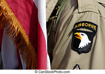 US soldier and flag of Airborne division during a...