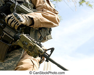 US soldier in camouflage uniform holding his rifle