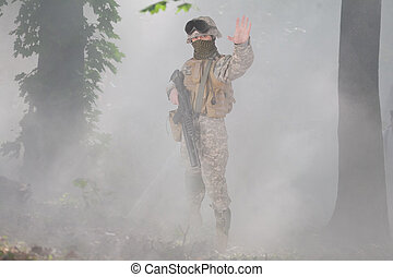 US soldier with assault rifle scouting in the foggy forest