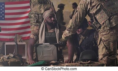 Close-up of dark-skinned male together with senior caucasian comrades gathered at table with army laptop developing plan to detect enemy forces. Squad of soldiers around computer in abandoned building