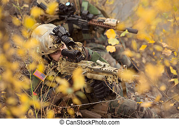 U.S. soldiers team aiming at a target of weapons