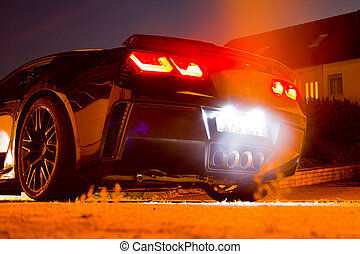 US sports car at night with glowing taillights