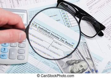 USA 1040 Tax Form 1040 with magnifying glass, glasses,...
