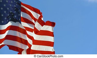 American Flag blowing in the wind with a blue sky background. USA American Flag. Waving United states of America famous flag in front of blue sky. Memorial Day, Independence Day - American concept.