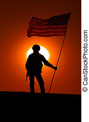 USA army soldier with flag on sunset background