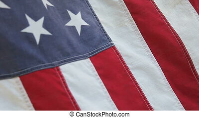 an old fabric American flag in a morning breeze