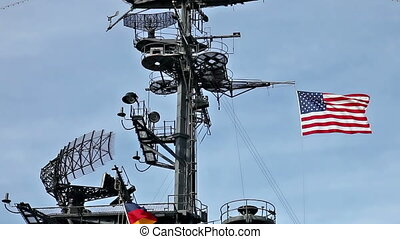 USA flag and antennas on carrier control tower in blue sky