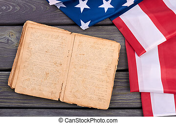 USA flag and old opened book.